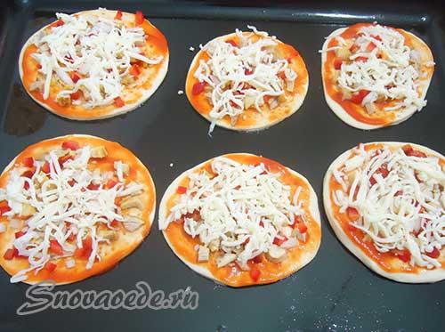посыпать мини пиццу натертым сыром